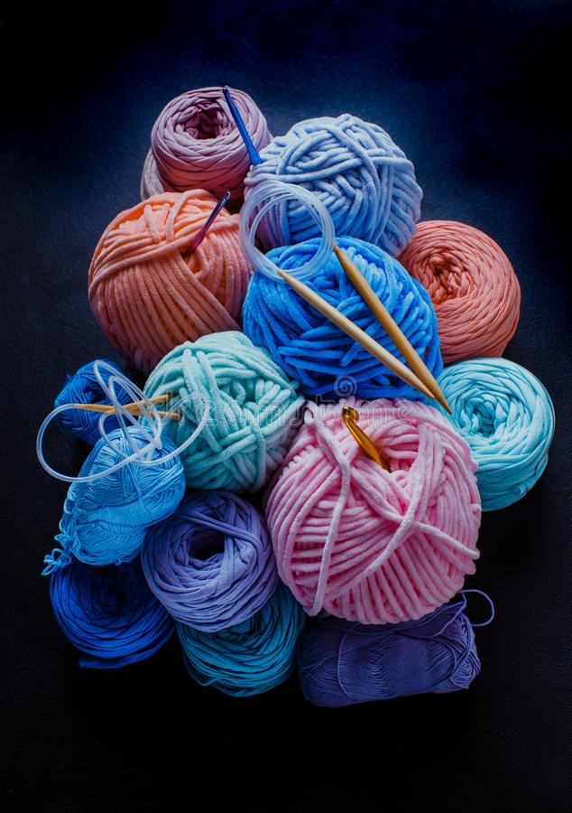 Hobby still life with yarn balls and crafts. Heap of plush and textile yarn balls with hooks and knitting needles. Hobby still life royalty free stock images
