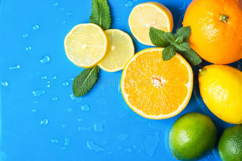 Heap of raw juicy citrus fruits oranges lemons lime fresh mint on wet blue background with water drops. Summer beverages. Refreshments drinks cocktails stock images