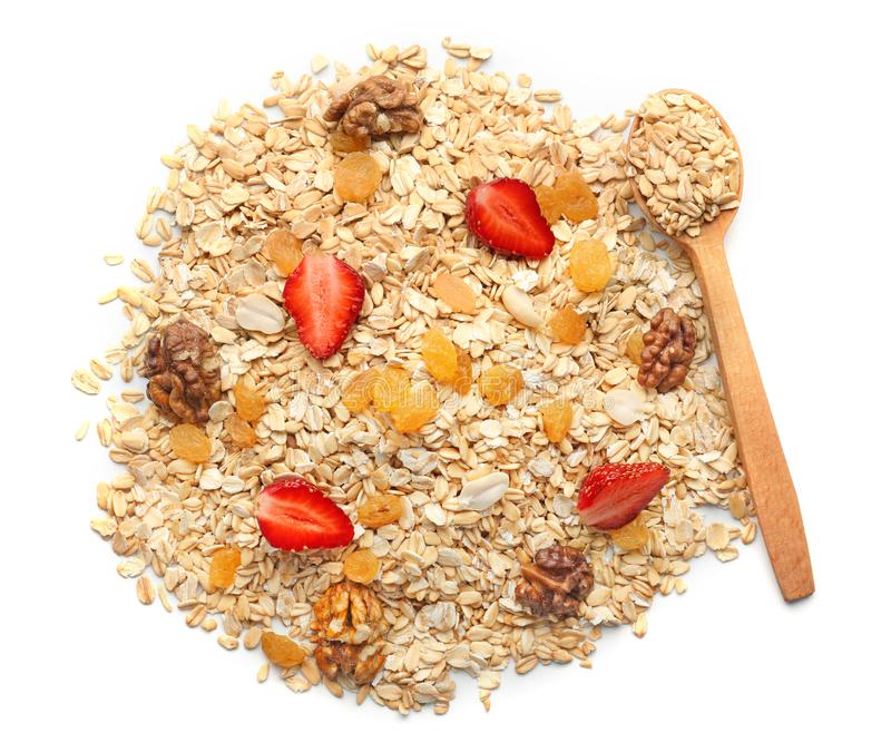 Heap of raw oatmeal with raisins, walnut and strawberry on white background stock image