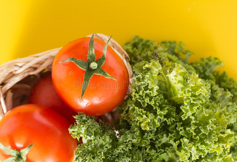 Heap of red cherry tomatoes and kale leaves, on yellow background. Heap of red cherry tomatoes and kale leaves, on vivid yellow background royalty free stock photography