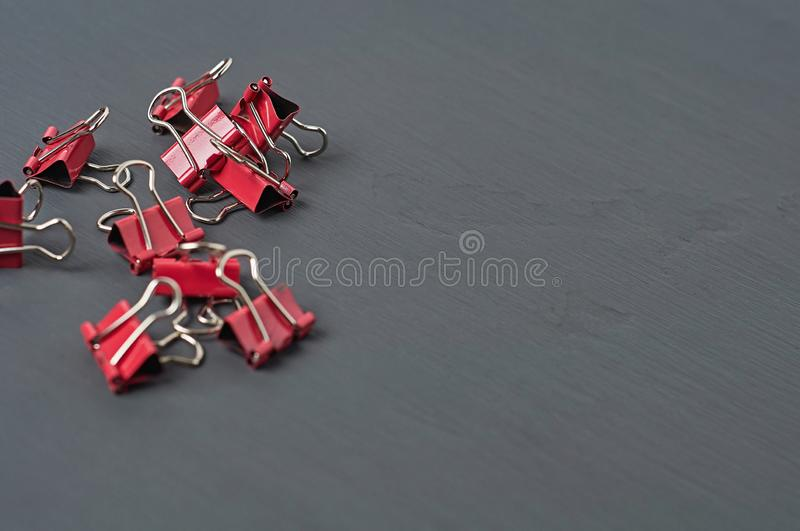 Heap of red metal binders for paper on dark concrete desk in office, school or home. Space for text royalty free stock photos
