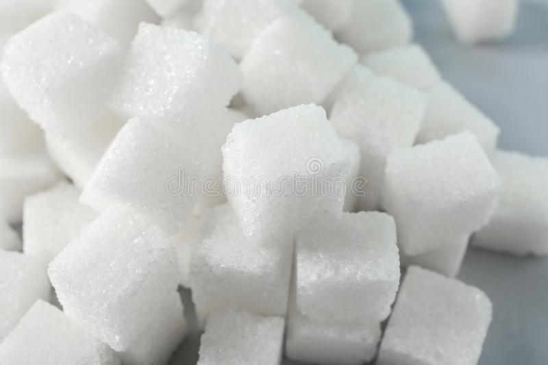 Heap of refined sugar cubes on table, closeup stock photo