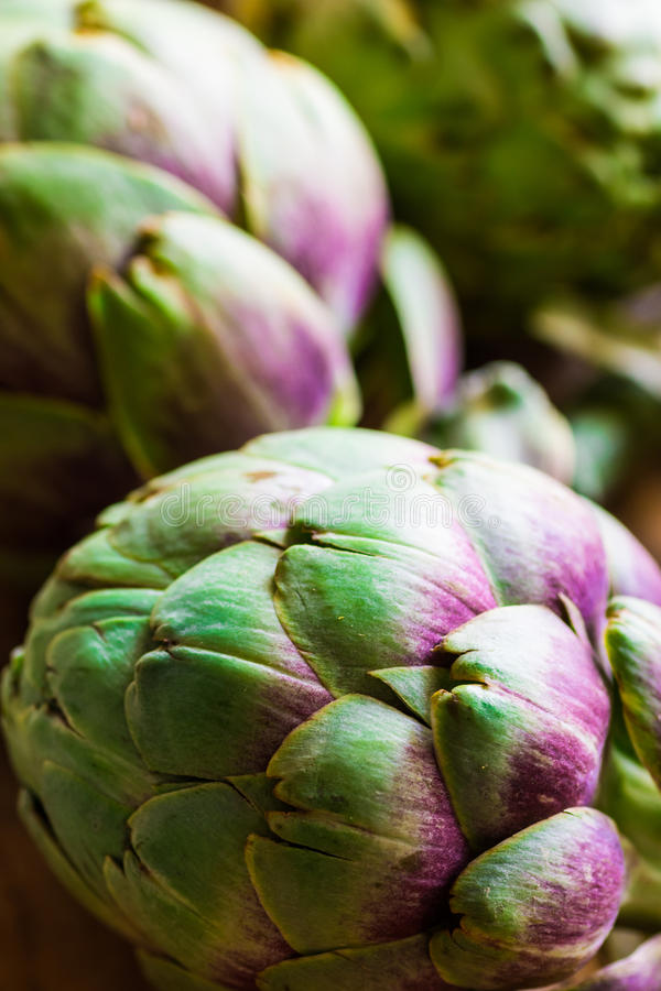 Heap of ripe colorful organic artichokes on plank wood table, natural light, rustic style, healthy food stock photo