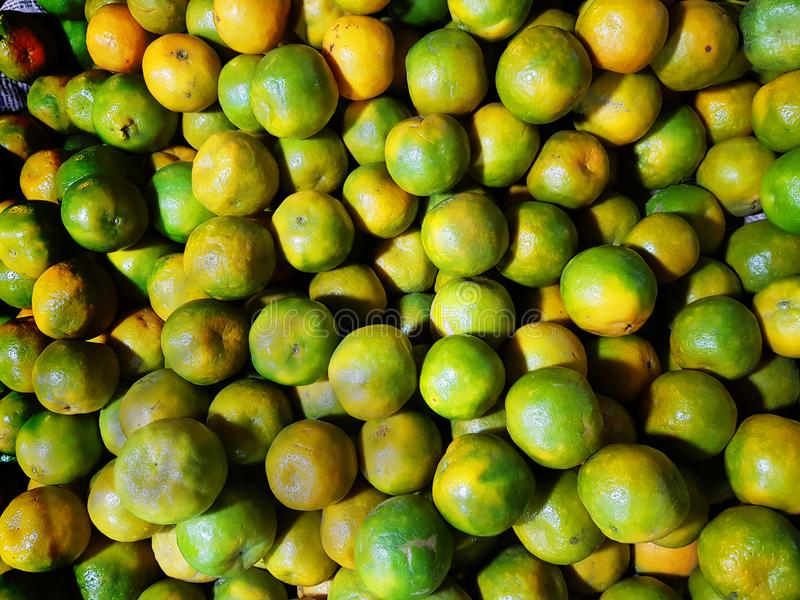 Heap of ripe green yellow sweet lemon mosambi lebu for sale in fruit market stock images