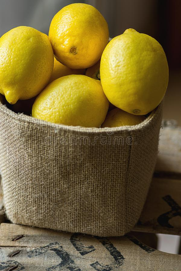 Heap of Ripe Organic Lemons in Jute Sack Standing on Wood Garden Box. Rustic Kinfolk Style. Atmospheric Mood Cozy Atmosphere. royalty free stock photos