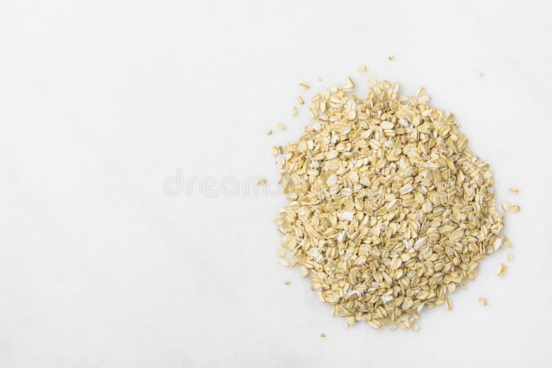 Heap of Rolled Oats Spilled on White Marble Stone Table. Healthy Lifestyle Nutrition Fiber Source Concept. Poster Banner Streamer with Copy Spac stock photography