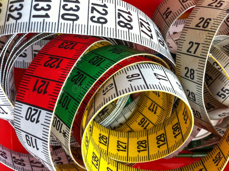 Heap of rolled up tape measure stock image