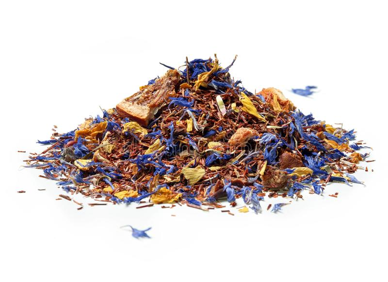 Heap of Rooibos tea with cornflower and orange slices isolated on white background. stock image