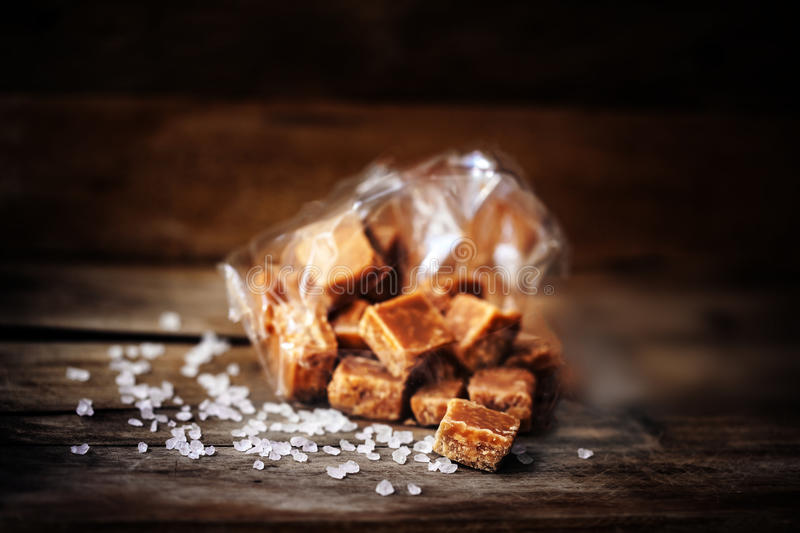 Heap of Salted caramel pieces and sea salt on a wooden table. Bu royalty free stock photography