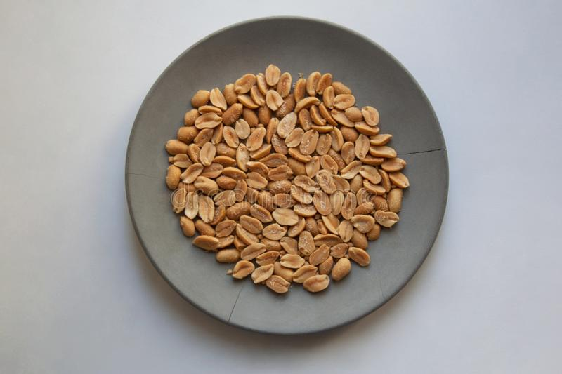 Heap of salted roast peanuts on grey plate from above stock photography
