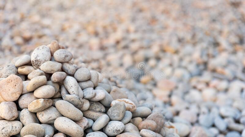Heap of sea pebbles on a shore, close-up. Natural summer background with soft copy space. Summer time theme stock images