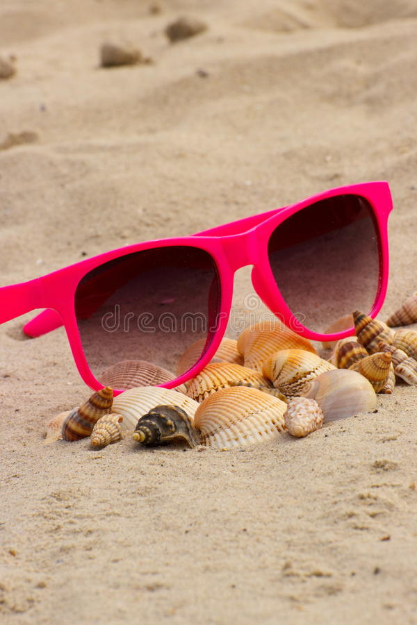 Heap of shells and pink sunglasses on sand at the beach royalty free stock photos