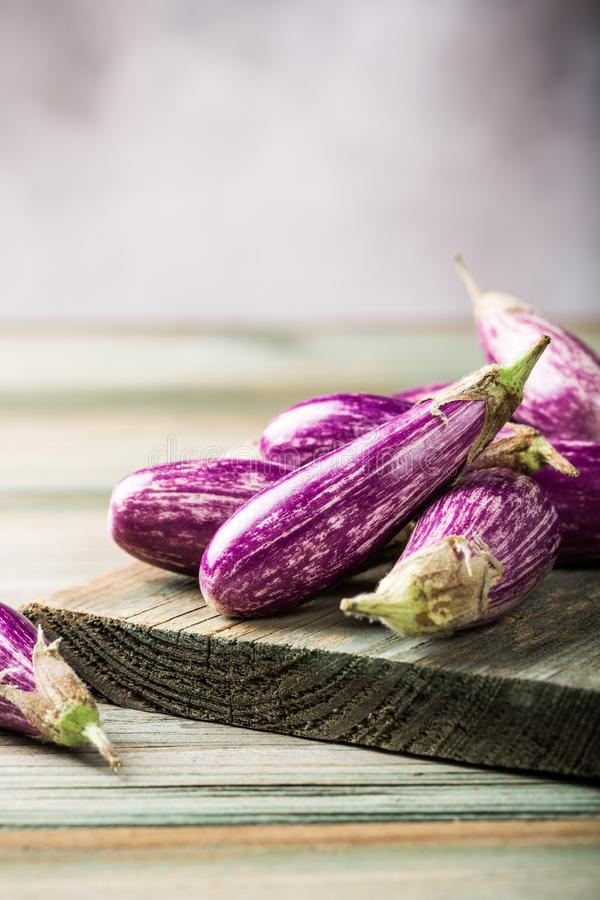 Heap of small eggplant or aubergine. Vegetable with basil leaves on old wooden background. Healthy food concept with copy space stock image