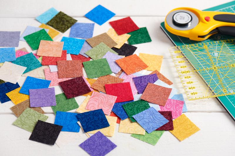 Heap square pieces of colorful fabrics on white wooden surface, quilting accessories stock photography