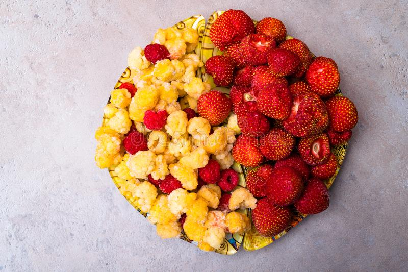 Heap of Sweet Strawberries and Juicy Raspberries Isolated on stone Background. Summer Healthy Food Concept. Food for heart health stock images