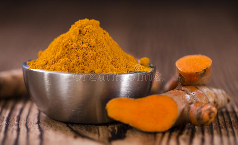Heap of Turmeric (selective focus). On an old wooden table royalty free stock photo