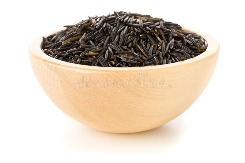 Heap of uncooked, raw, black wild rice grains in wooden bowl over white royalty free stock image