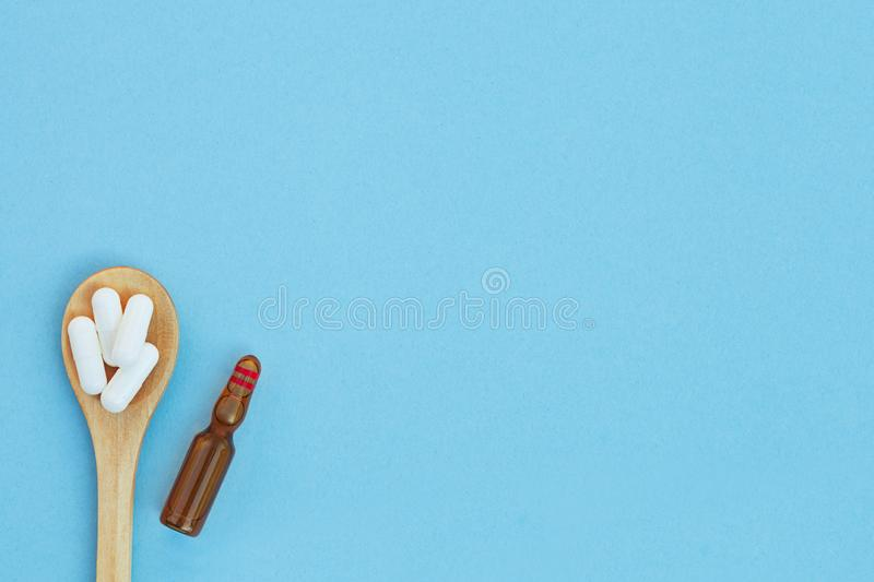 Heap of white medical pills in wooden spoon and ampule for injection  on blue background, top view royalty free stock photography