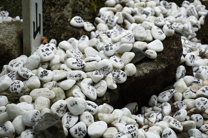 Heap of white pebble stones with religious wishes in the Japanese temples (Shinto shrines) royalty free stock photos