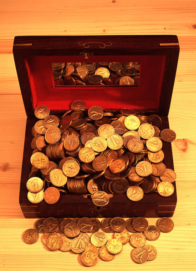 Heaped of gold coins. On a wooden table stock image