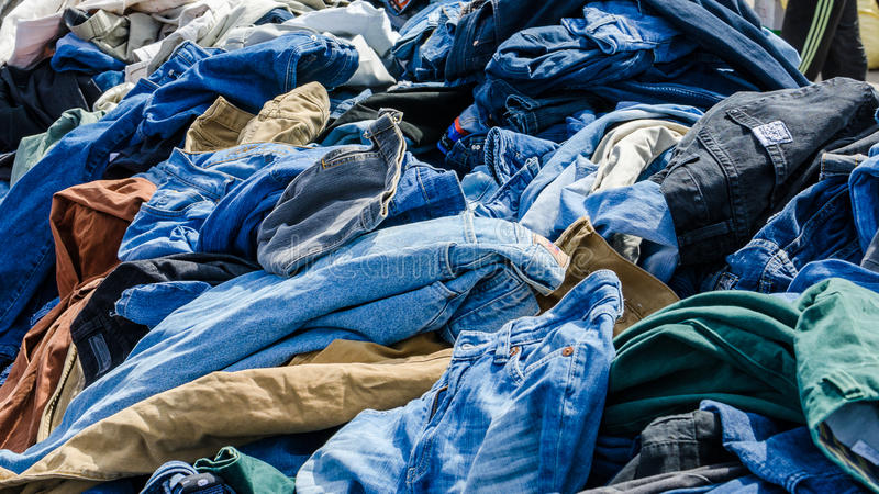 Heaps of clothing on the second hand market stock images