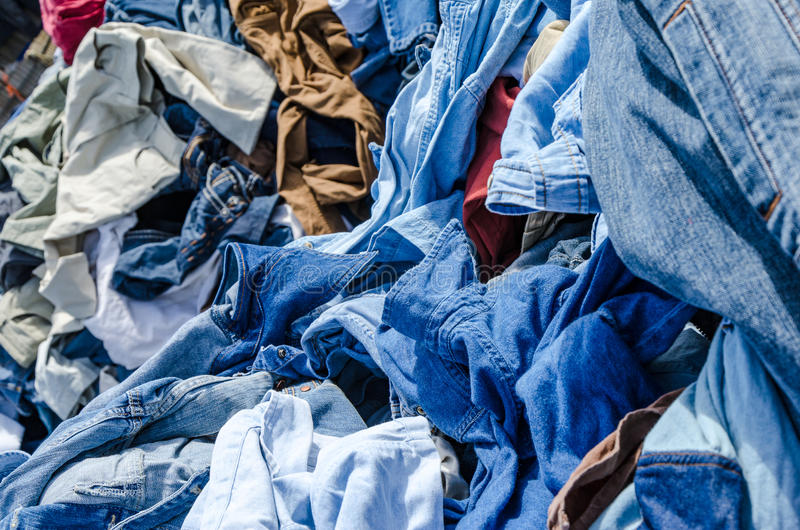 Heaps of clothing on the second hand market stock photography