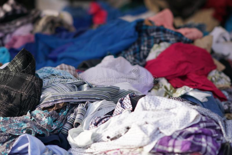 Heaps of clothing on second hand market stock photos