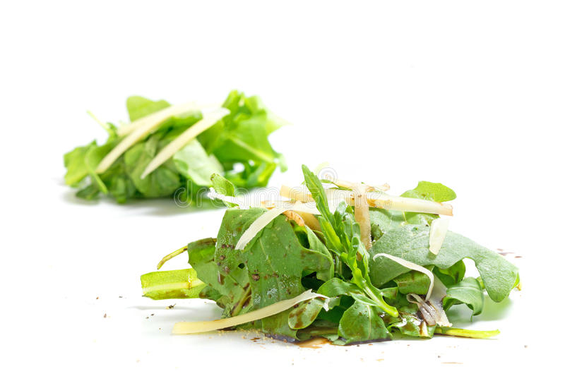 Heaps of rucola salad with parmesan and balsamic vinegar isolat. Small heaps of rucola salad with parmesan cheese garnish and balsamic vinegar as a light and stock photography