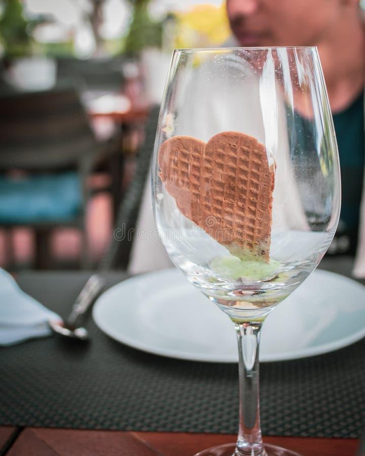 Hear ha modellato il biscotto in vetro di vino, fotografia stock libera da diritti