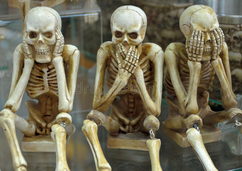 Hear no evil, speak no evil, see no evil. Skeletons on a pedestal posed as hear no evil, speak no evil, see no evil stock photography