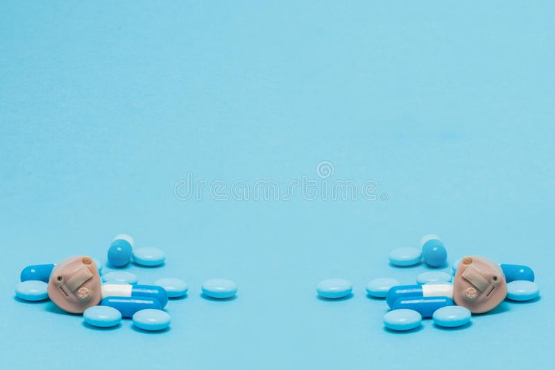 Hearing aid and blue pills on blue background. Medical, pharmacy and healthcare concept. Copy space. Empty place for text or logo.  stock photo