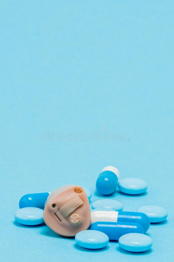 Hearing aid and blue pills on blue background. Medical, pharmacy and healthcare concept. Copy space. Empty place for text or logo.  stock photography