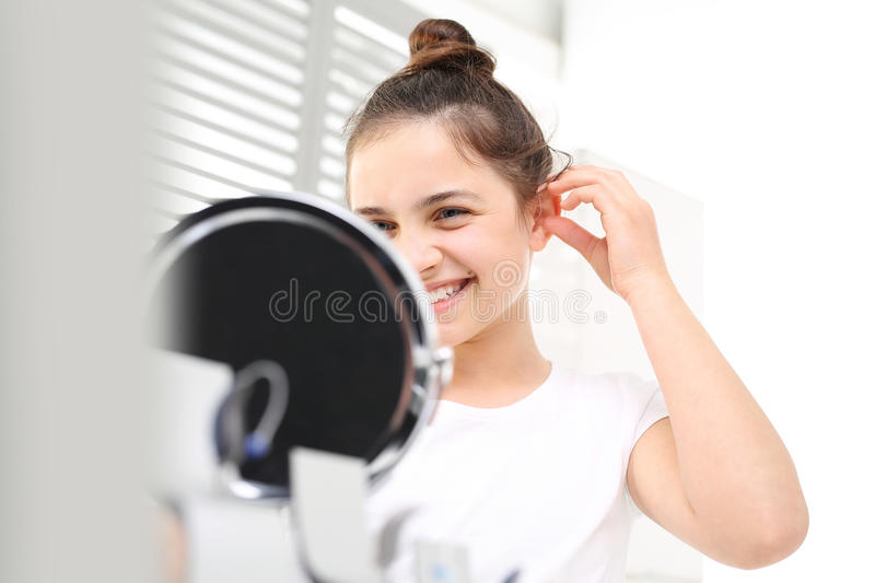 Hearing aid. Cheerful girl assumes hearing aid viewing in the mirror royalty free stock images