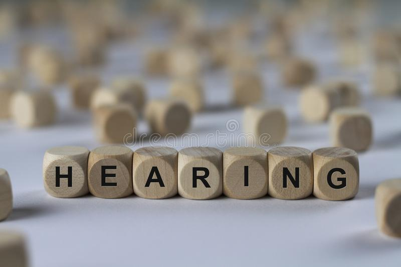 Hearing - cube with letters, sign with wooden cubes. Hearing - wooden cubes with the inscription `cube with letters, sign with wooden cubes`. This image belongs stock photography