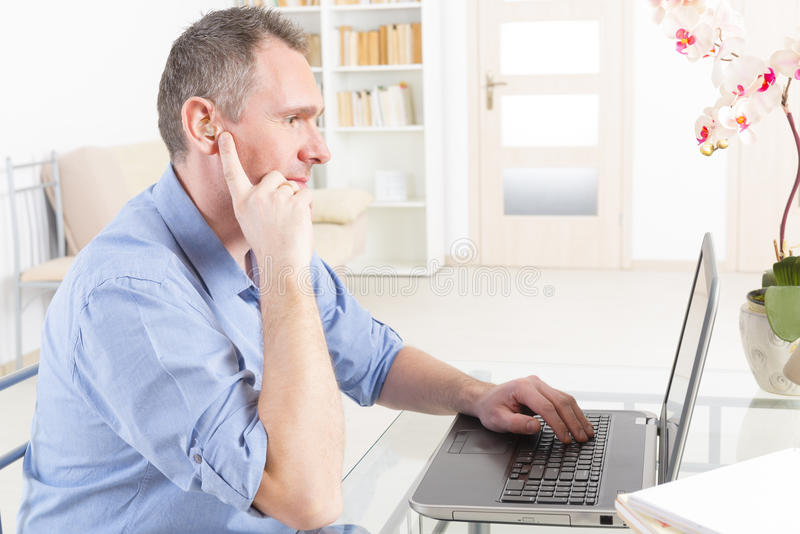 hearing impaired man working with laptop stock image