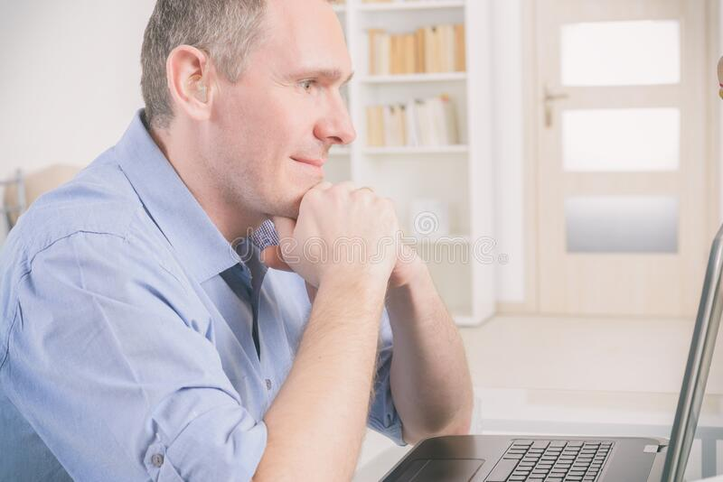 Hearing impaired man working with laptop and mobile phone stock photography