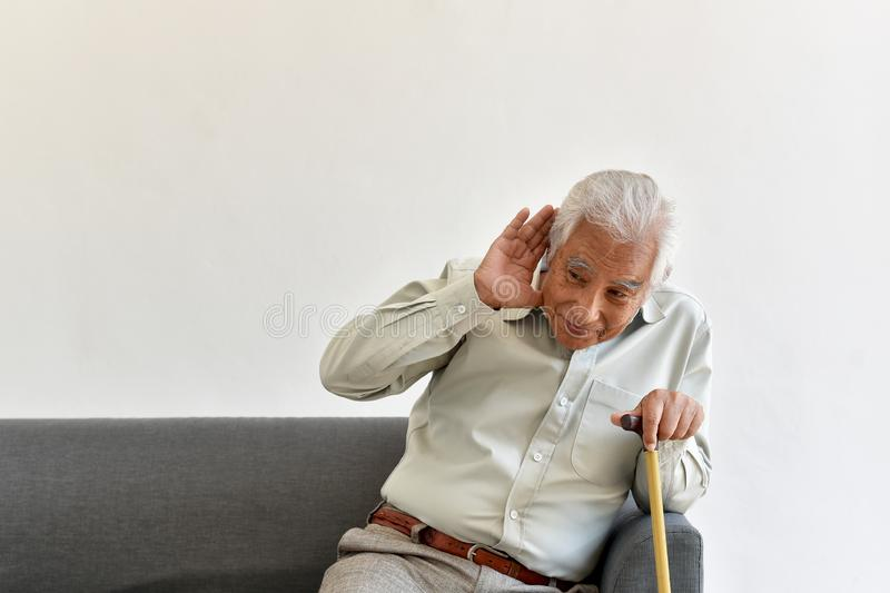 Hearing loss problem, Asian old man with hand on ears gesture trying to listen. stock images