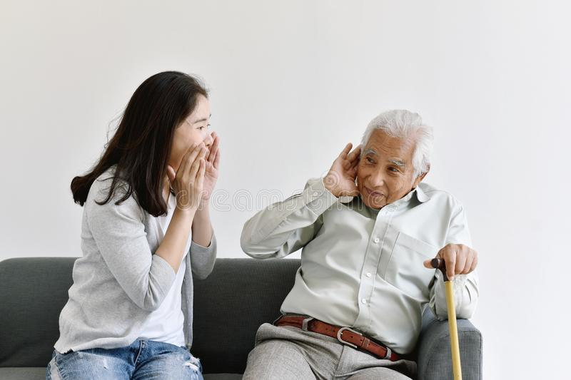 Hearing loss problem, Asian old man with hand on ear gesture trying to listen shouting woman. stock photos