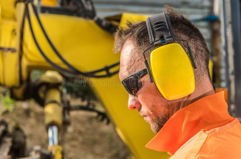 Hearing Protection Headset. Noise Reduction Hearing Protection Headset. Caucasian Construction Contractor Wearing Sunglasses and Headphones royalty free stock image