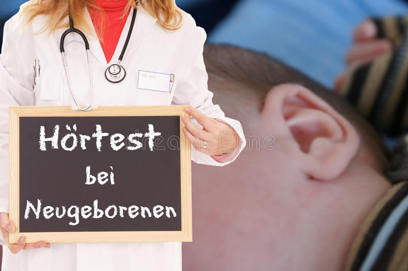 Hearing Test. Doctor with shield and the german words Hearing screening for newborns royalty free stock photography