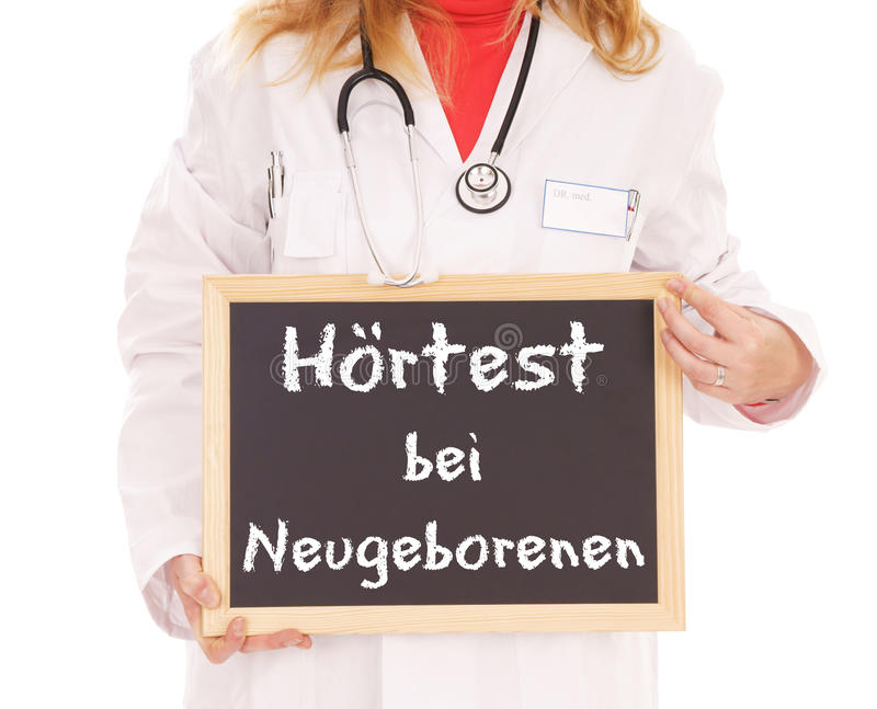 Hearing Test. Doctor with shield and the german words Hearing screening for newborns stock photography