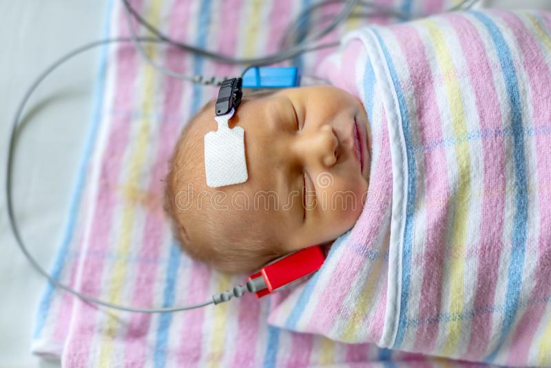Hearing test of a sleeping newborn at hospital. Nursery with cables attached royalty free stock image