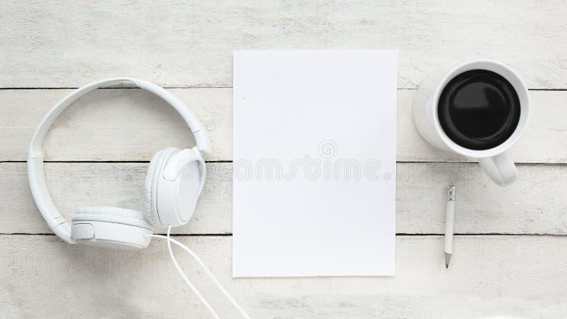 Hearphones, pusty papier, kubek cofee i pióro na białym drewnianym biurku, obrazy stock