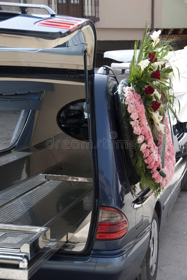 Hearse. Black hearse with a wreath of flowers ready to go to funeral royalty free stock image