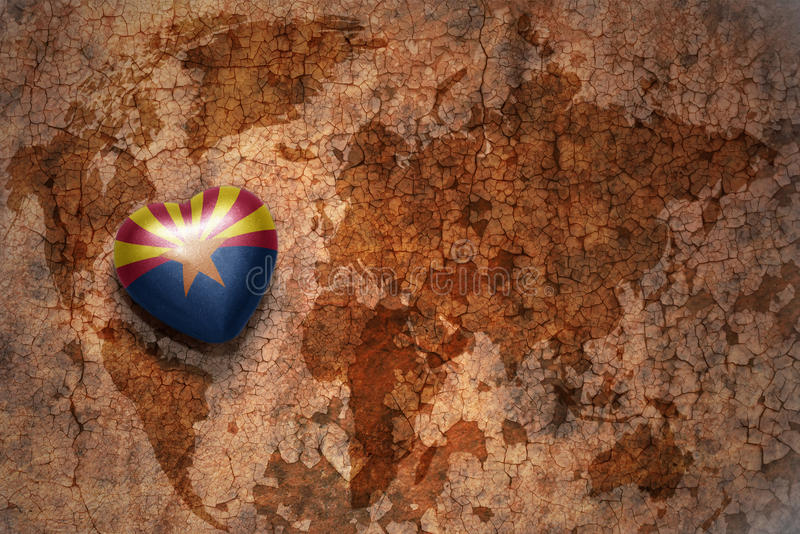 Heart with arizona state flag on a vintage world map crack paper background stock photography