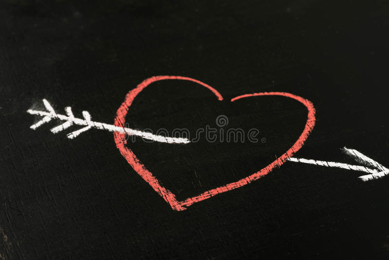 heart and arrow chalk drawing on blackboard selective focus macro royalty free stock images