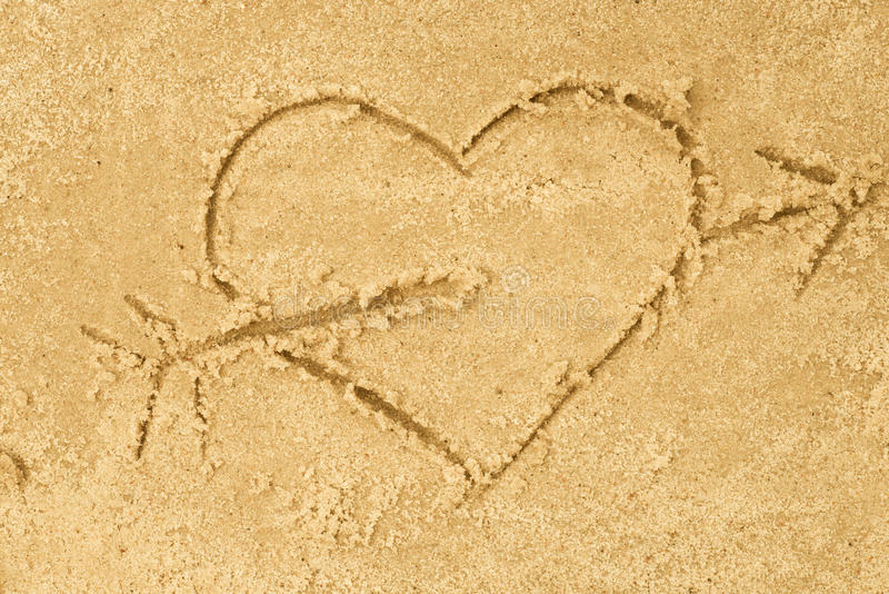 Heart and arrow drawing in sand royalty free stock images