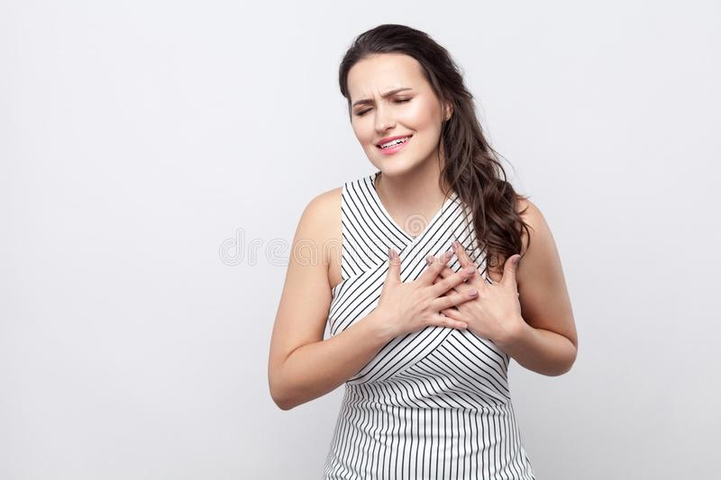 Heart attack or broken heart. Portrait of sad beautiful young brunette woman with makeup and striped dress standing and holding stock photography
