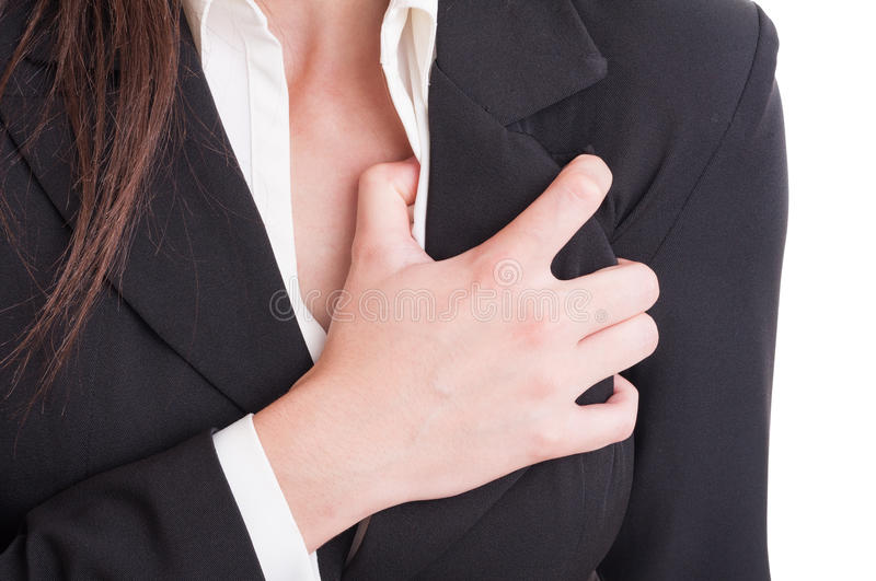 Heart attack or cardiac arrest gesture made by suited woman. Closeup with hand grabbing chest pain royalty free stock image