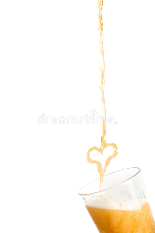 Heart of beer pouring into a glass. On white background royalty free stock photography